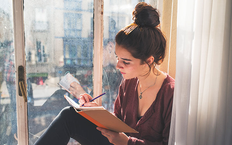 A white woman with hair in a messy bun on her head imagines how to journal as she sits on a windowsill overlooking a city and writes in her journal.