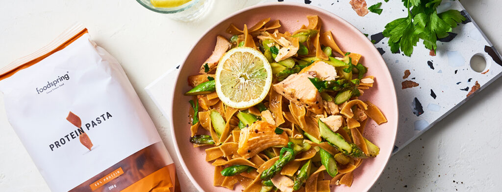 a salmon-pink-colored bowl filled with pasta with salmon and asparagus, garnished with a moon of fresh lime