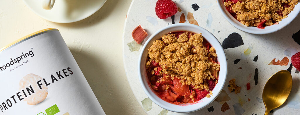 A white ramekin holds a pink-red portion of low-sugar rhubarb crumble topped with golden-brown streusel