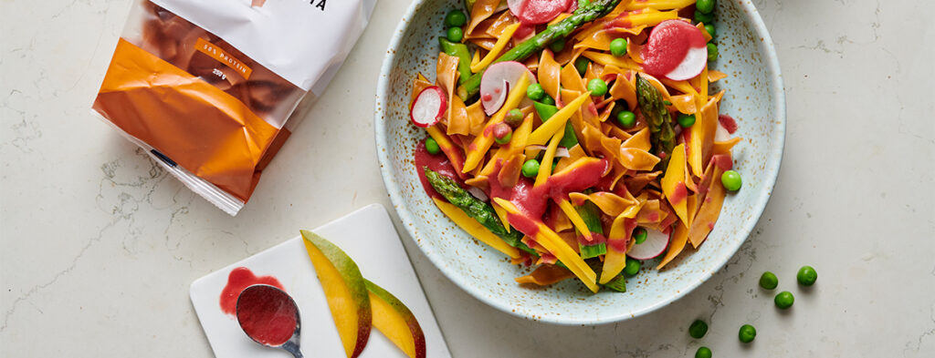a big, colorful protein pasta salad with fresh vegetables and a delectable dressing is seen from above on a white plate