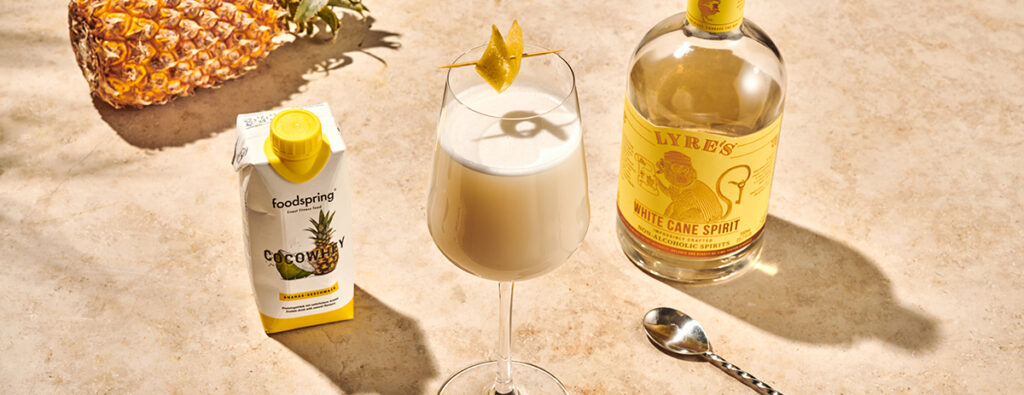 A wine glass filled with protein pina colada and with a carton of Pineapple CocoWhey on the side